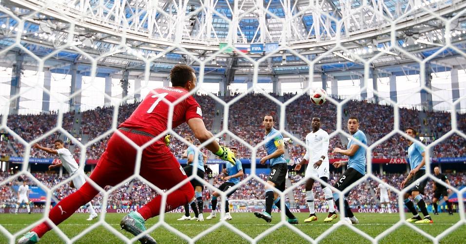 Raphael Varane sobe mais que todos e cabeceia para o gol, sem chance para Muslera, abrindo o placar para a França contra o Uruguai