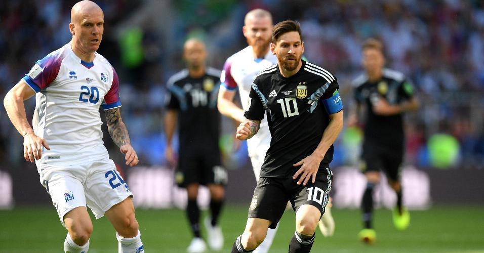Lionel Messi, da seleção da Argentina, carrega a bola e é observado por Emil Hallfredsson, da Islândia