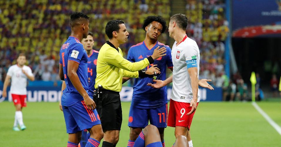 Juan Guillermo Cuadrado, da Colômbia, reclama com Robert Lewandowski, da Polônia, após pisão em Yerry Mina