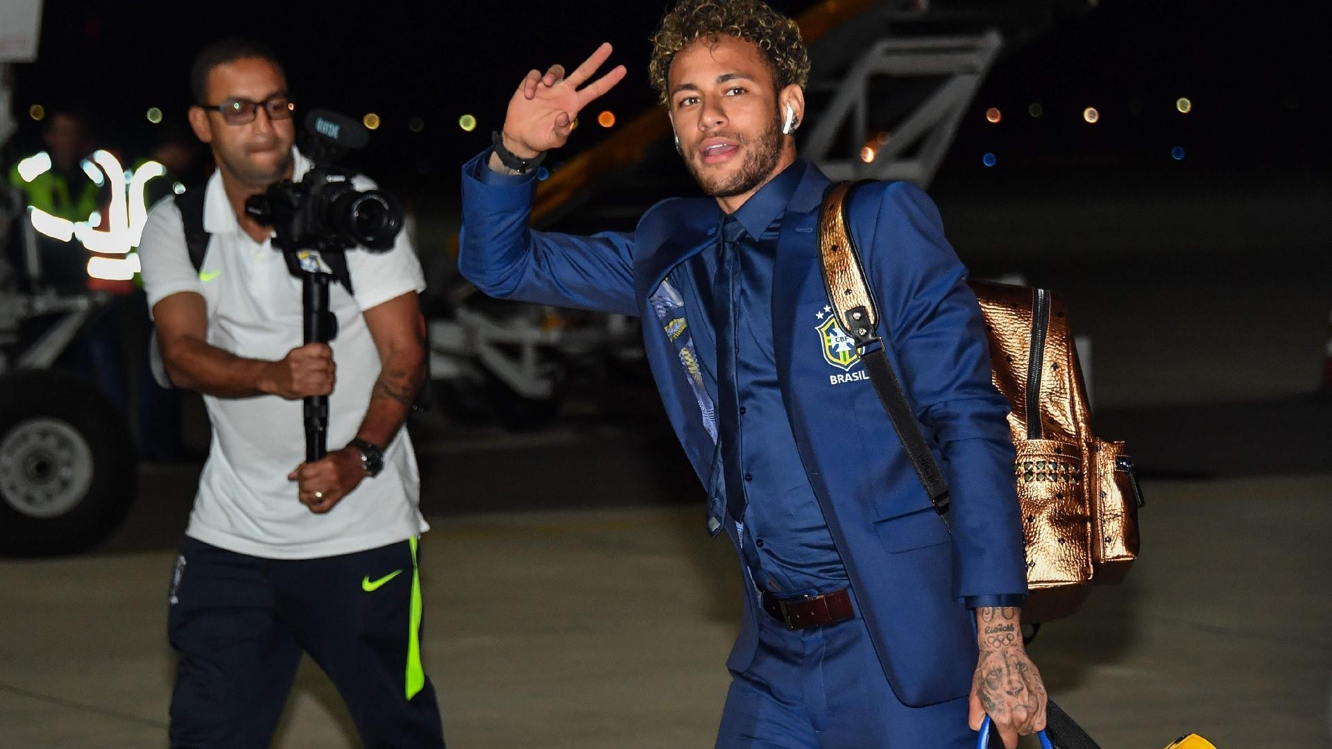 Neymar acena para a imprensa durante desembarque