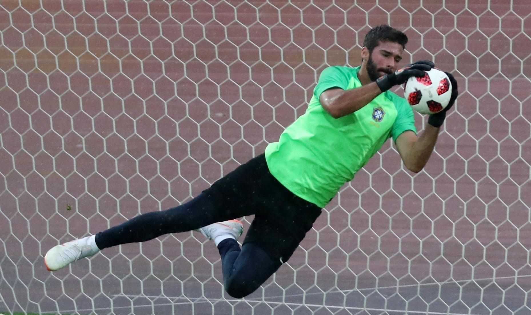 Alisson salta para fazer defesa durante treino da seleção brasileira