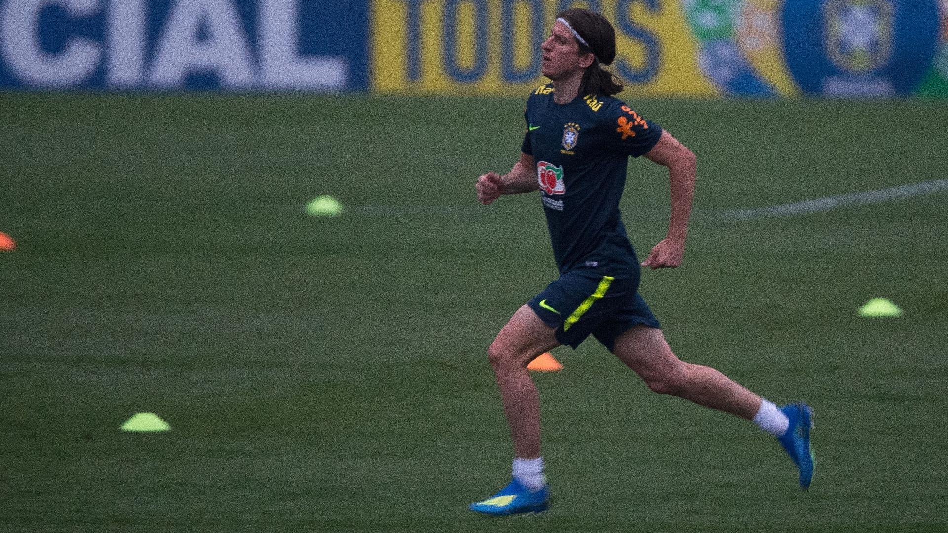 Filipe Luís corre durante treino em campo da seleção brasileira
