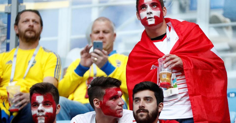 Torcedores da Suíça com os da Suécia ao fundo antes de duelo entre as seleções dos dois países