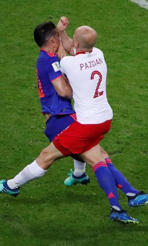 James Rodríguez, da Colômbia, se choca com o zagueiro Michal Pazdan, da Polônia