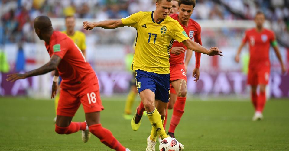 Viktor Claesson, da Suécia, conduz a bola seguido por Dele Alli, da Inglaterra