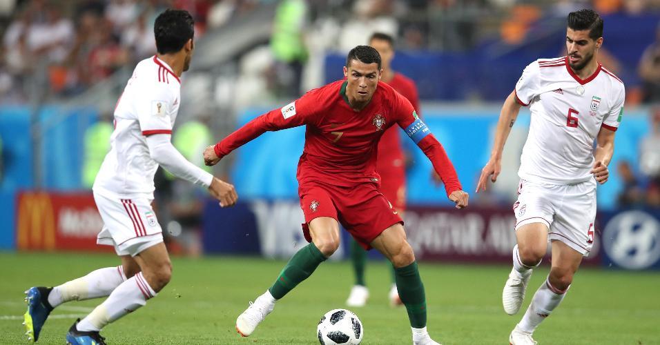 Cristiano Ronaldo, de Portugal, é cercado por Saeid Ezatolahi e Vahid Amiri, do Irã