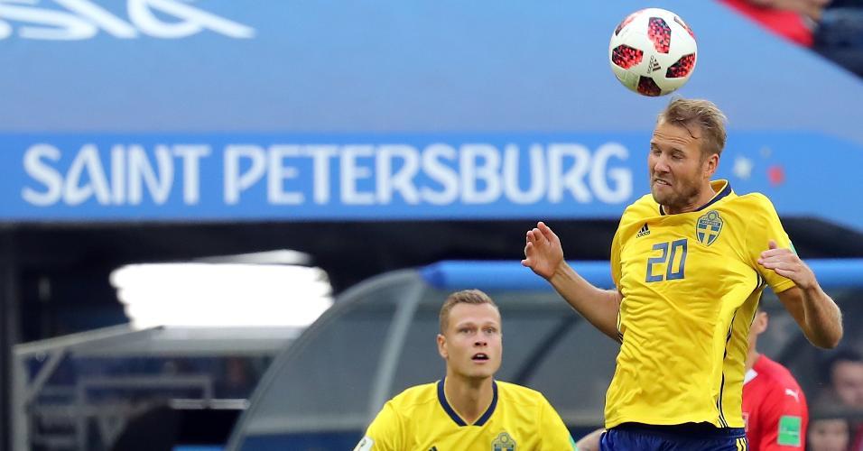 Ola Toivonen, da Suécia, cabeceia a bola no jogo contra a Suíça observado por Viktor Claesson