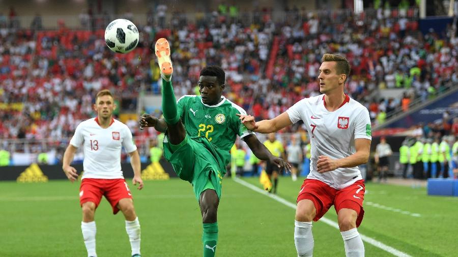 Moussa Wague, do Senegal, chuta a bola enquanto é observado por Arkadiusz Milik, da Polônia - Shaun Botterill/Getty Images