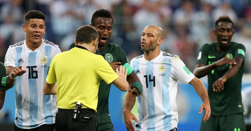 Ensanguentado, Javier Mascherano reclama com o árbitro Cuneyt Cakir durante Argentina x Nigéria