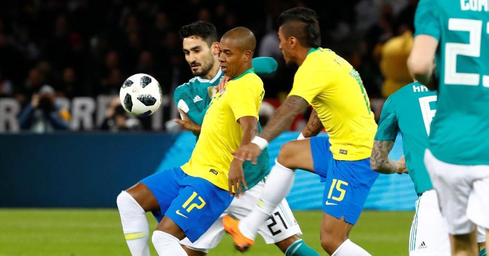 Fernandinho e Paulinho disputam bola no meio-campo com Gundogan