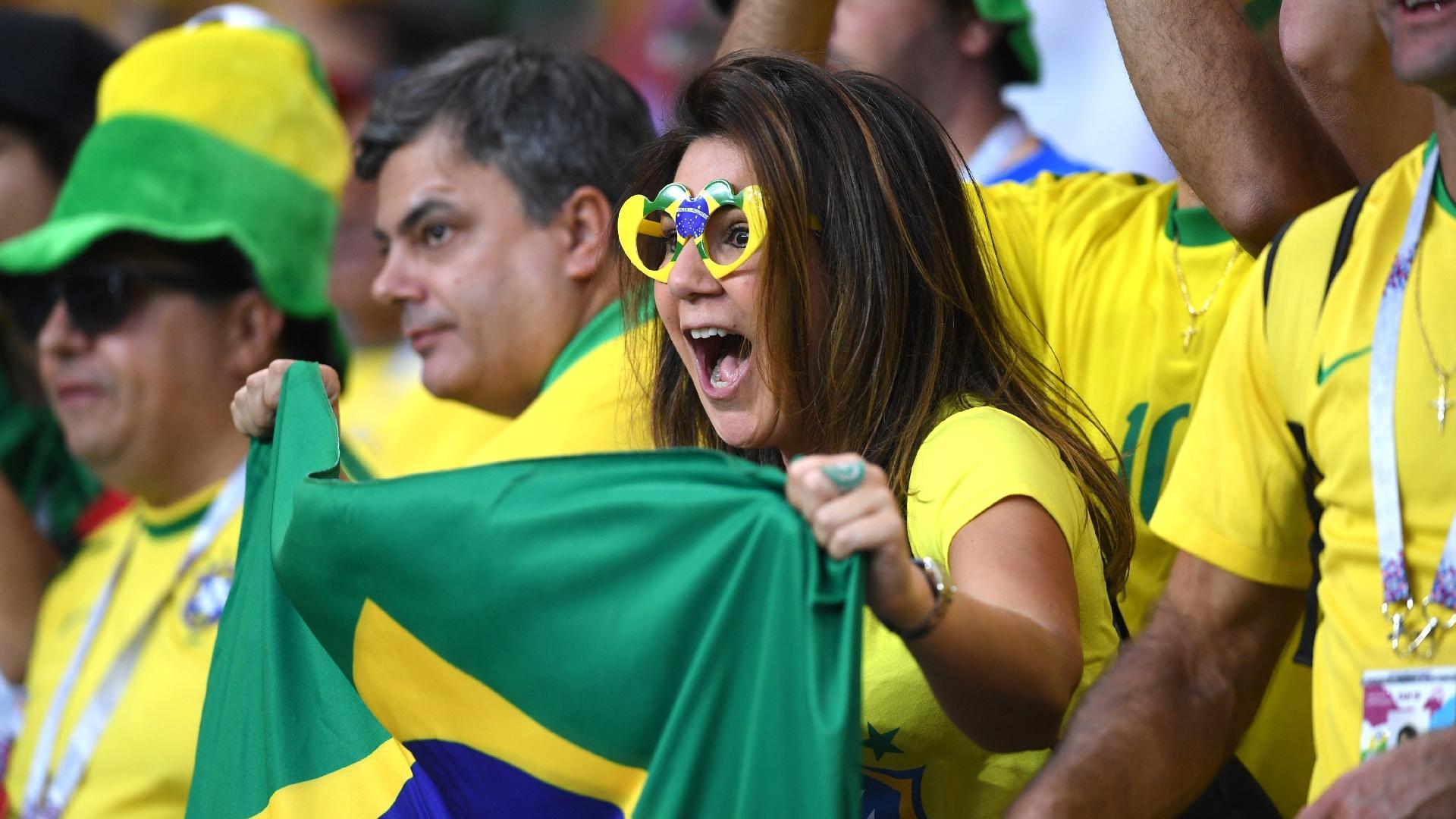 Vestida de verde e amarelo da cabeça aos pés, torcedora grita pelo Brasil