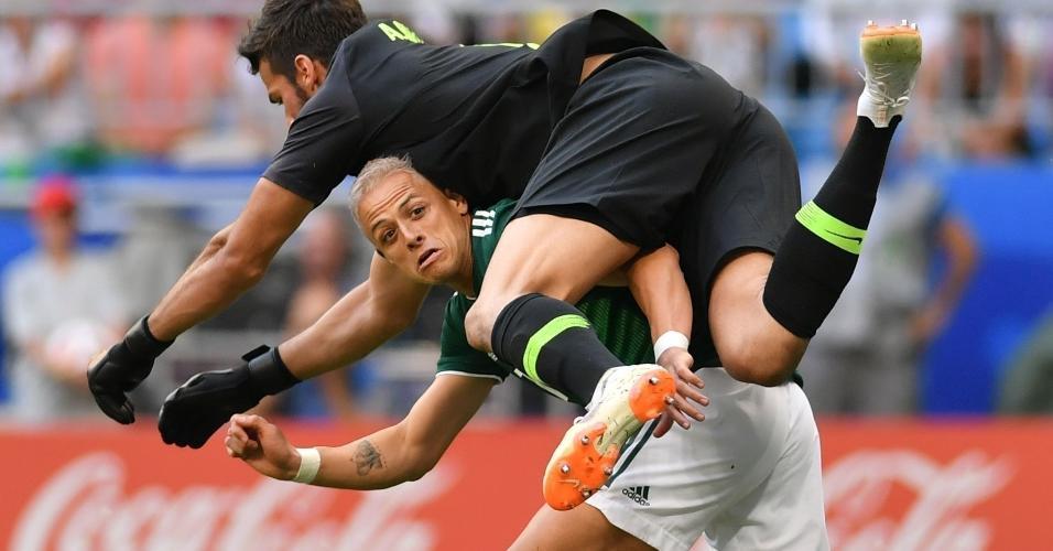 Alisson tromba com Chicharito em disputa de bola na área