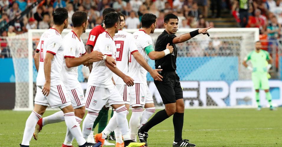 Jogadores do Irã se revoltam com Enrique Cáceres após o árbitro apontar pênalti depois de consultar o árbitro de vídeo