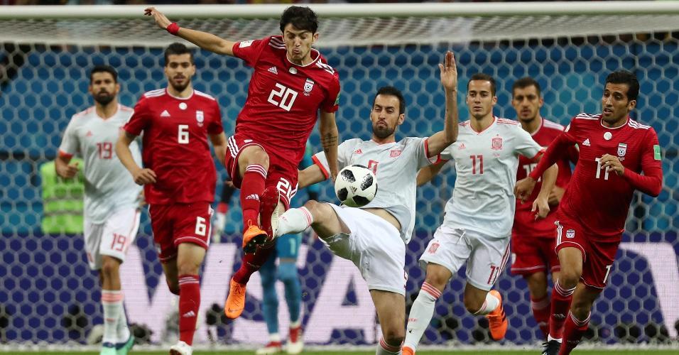 Sardar Azmoun, do Irã, tenta disputar bola com Sergio Busquets, da Espanha