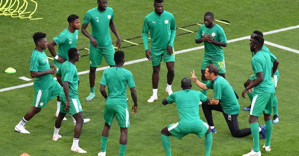 Atletas de Senegal se aquecem pouco antes de jogo contra a Colômbia