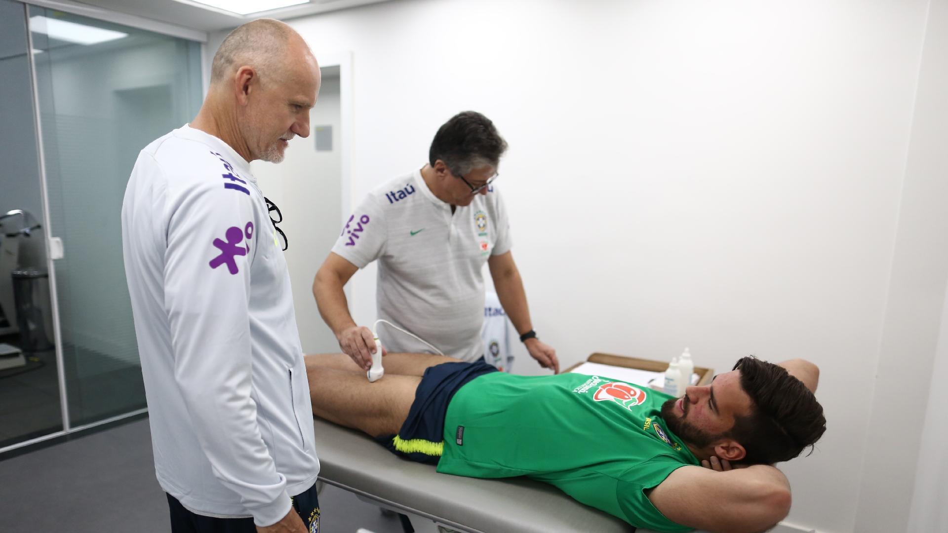 Alisson conversa com Taffarel enquanto é examinado pelo departamento médico da seleção