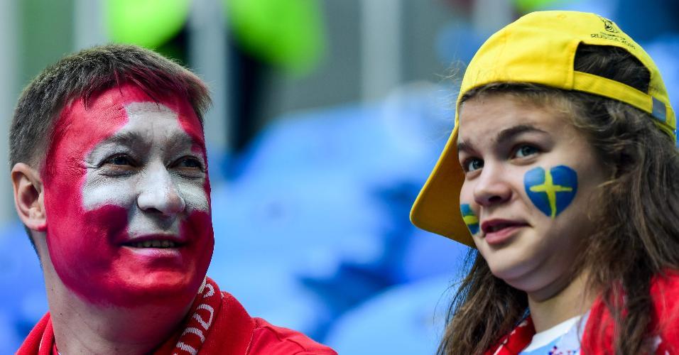 Homem com bandeira da Suíça e mulher com a da Suécia nos rostos