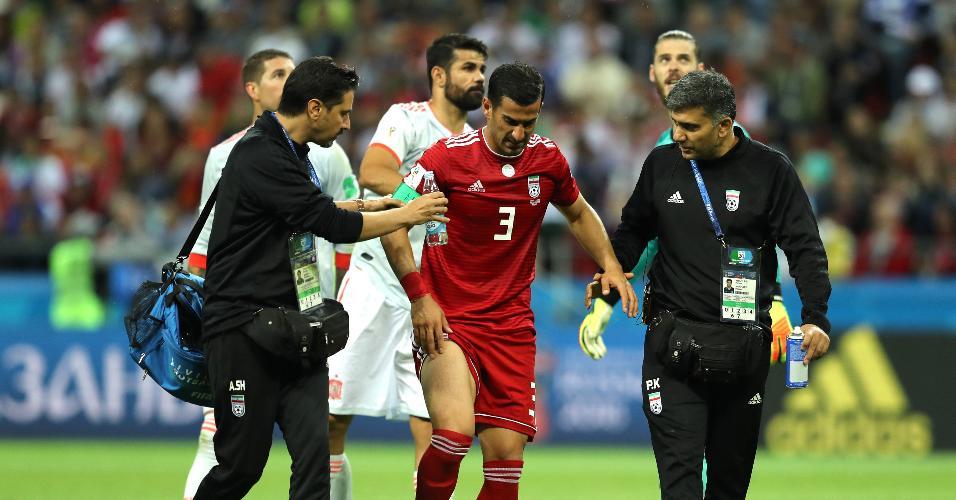 Ehsan Haji Safi, capitão do Irã, é atendido pelos médicos após sentir dores em jogo contra a Espanha