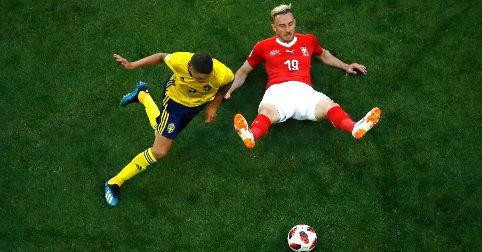 Josip Drmic, da Suíça, no chão enquanto Mikael Lustig, da Suécia, corre atrás da bola