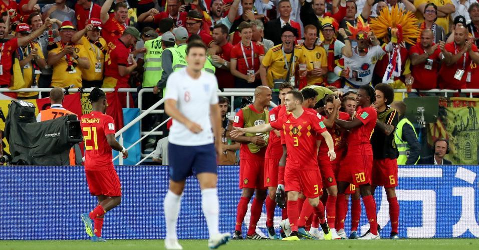 Harry Maguire lamenta revés parcial da Inglaterra enquanto jogadores da Bélgica comemoram gol de Januzaj