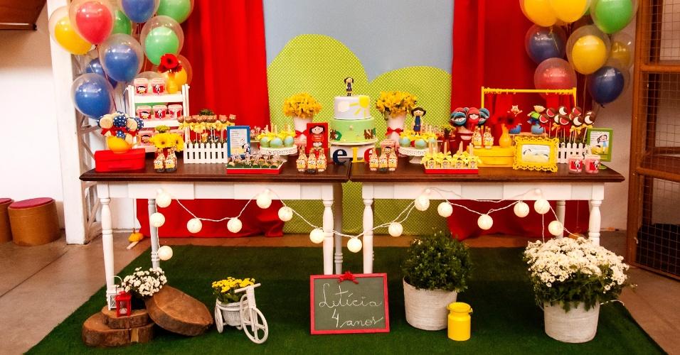Para a parede da mesa do bolo, Rosângela Ribeiro, da Mariah Festas, confeccionou uma cortina vermelha com a paisagem que costuma aparecer no desenho quando Luna e sua turma apresentam  o que aprenderam naquele episódio. Vasos, bicicletas e peças de madeira também foram utilizadas para ambientar o jardim do desenho