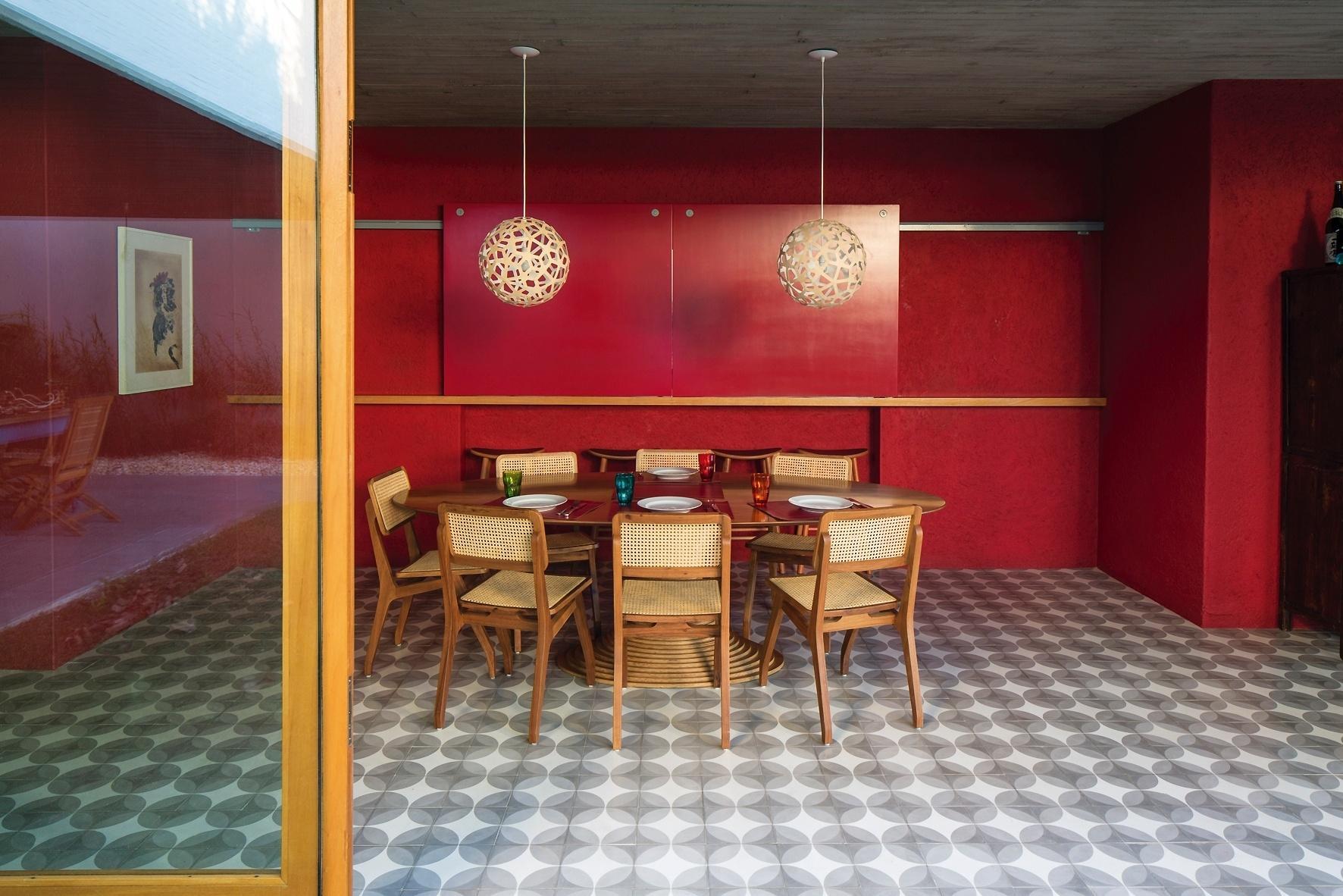 A aconchegante ambientação da sala de jantar é aquecida pelo vermelho das paredes. O cômodo é iluminado naturalmente graças à interligação com o pátio central, através de portas de correr envidraçadas. A mesa com pé centralizado é cercada pelas cadeiras de palhinha. O projeto arquitetônico da casa Lapa leva a assinatura do escritório Brasil Arquitetura