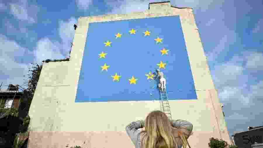 Jovem observa mural de Banksy em Dover - REUTERS/Hannah McKay