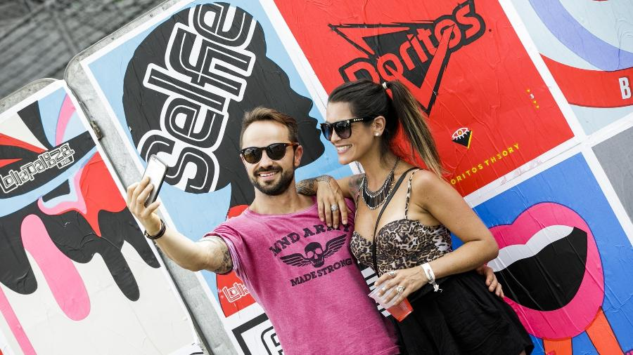 O casal Frederico Castro e Fernanda Faro tiram selfie em frente a pôster no Lollapalooza Brasil 2018 - Mariana Pekin/UOL