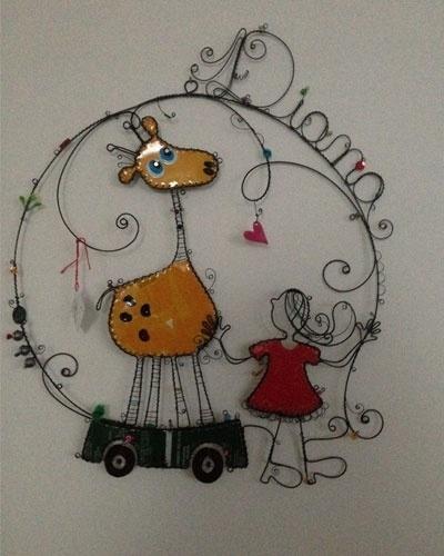 Guirlanda aramada de menina com girafa, da Coisas da Doris (doris@coisasdadoris.com.br). A peça mede 35 cm por 35 cm. R$ 400. Preço pesquisado em agosto de 2015 e sujeito a alterações