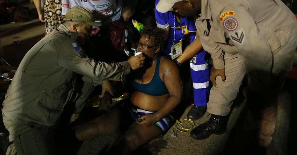 7.fev.2016 - Integrante passa mal e é hidratada, após desfilar na 1ª noite da Sapucaí