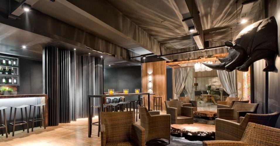 O Open Bar Miami, com 74 m², é um projeto do arquiteto Marcelo Lopes e mistura elementos como fibra natural e couro em um clima luxuoso. Na parede, uma cabeça de rinoceronte (à dir.) deixou o ambiente, que foi trabalhado em tons terrosos e escuros, com mais personalidade