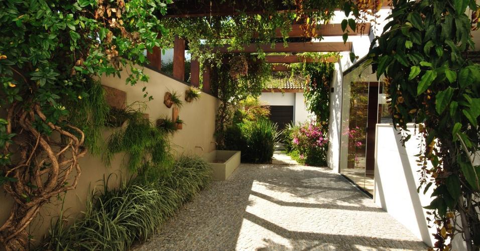 No projeto em Vinhedo (SP), do paisagista Alexandre Galhego, o pergolado foi apoiado no muro e na parede da casa. O intuito era filtrar o sol da tarde na área 'gourmet'. Executada em madeira (garapeira), a estrutura foi envernizada e coberta com a trepadeira sapatinho-de-judia (Thunbergia mysorensis)