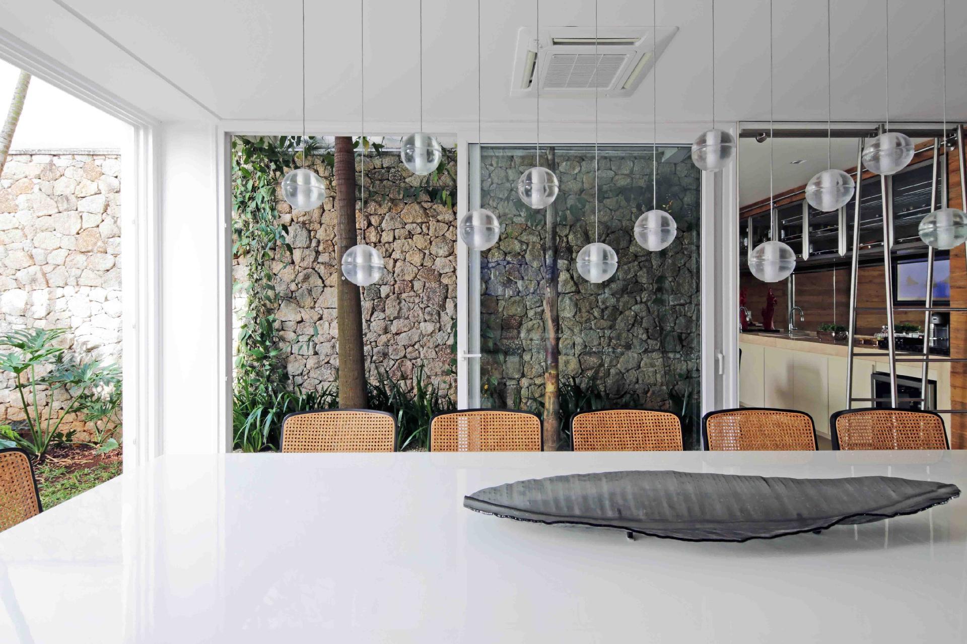 A parede de pedra percorre toda a extensão da área externa e do espaço 'gourmet' integrado à cozinha. Agradável, o ambiente é usado pela família em todas as refeições. A casa do condomínio Bauhaus é um projeto da arquiteta Monica Drucker