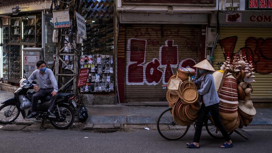 Vendedores utilizam máscaras para circularem por Hanoi, no Vietnã - Getty Images