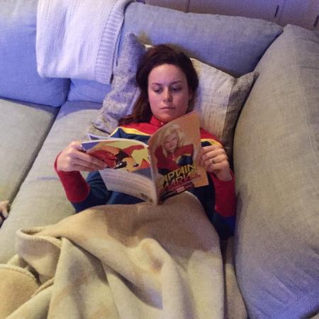 6.ago.2016 - Caracterizada com o uniforme da Capitã Marvel, Brie Larson lê gibi da heroína que vai interpretar no cinema - Reprodução/Twitter/brielarson