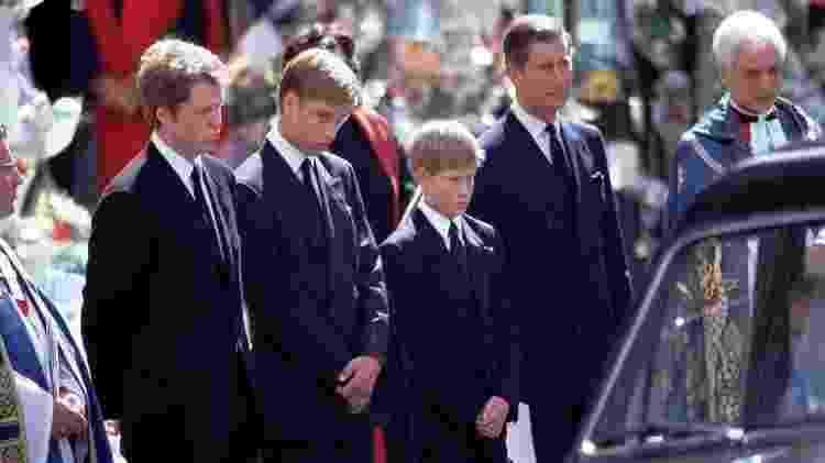 Príncipe Harry ficou ao lado do pai, príncipe Charles, e do irmão mais velho, príncipe William, enquanto viam o carro fúnebre carregar o caixão de Diana - BBC