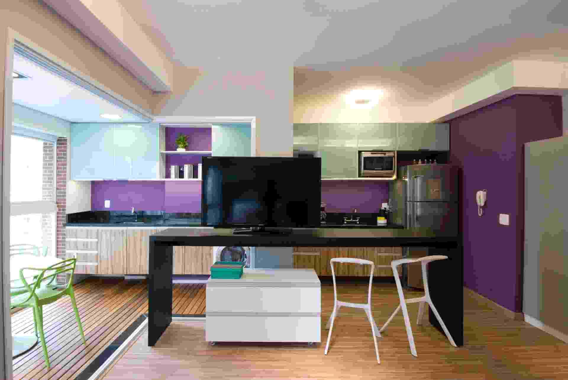 A fim de aproveitar melhor os espaços, Leandro Matsuda resolveu integrar a varanda com os ambientes internos, removendo as portas de vidro que separavam as áreas (à esq.). Ao fundo, as paredes pintadas com tinta lavável roxa substituem os azulejos. A cor cria um visual descontraído para o apartamento com 35 m² - Leandro Matsuda/ Divulgação