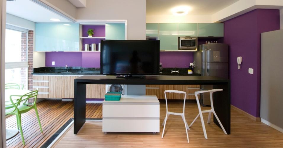 A fim de aproveitar melhor os espaços, Leandro Matsuda resolveu integrar a varanda com os ambientes internos, removendo as portas de vidro que separavam as áreas (à esq.). Ao fundo, as paredes pintadas com tinta lavável roxa substituem os azulejos. A cor cria um visual descontraído para o apartamento com 35 m²