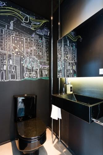 Um lavabo atende a área de convivência integrada do apartamento Alvorada. As paredes foram pintadas de preto e receberam desenhos a giz da artista Andrea Brazil. As louças são da Deca e reforçam o clima nortuno. Para finalizar, a cuba e o espelho são fixados por meio de elementos de serralheria no projeto do escritório Suite Arquitetos