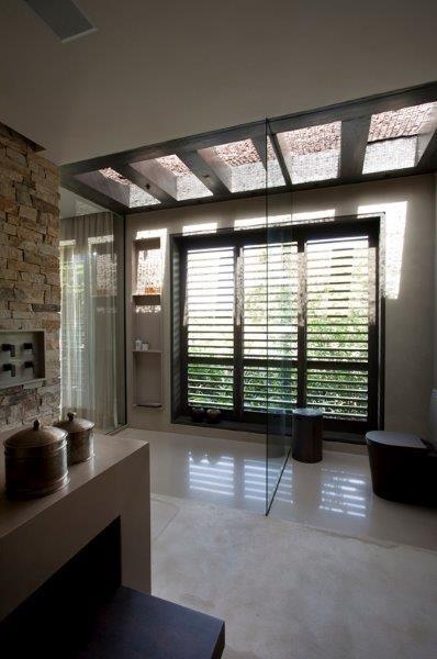 No banheiro da suíte principal da casa Areia, o pergolado em madeira e a cobertura de vidro trazem luz natural à área de banho (à esq.), que fica separada do sanitário por um pano de vidro. A sala de banho é ampla e aconchegante, como os demais ambientes da residência assinada pela arquiteta Debora Aguiar