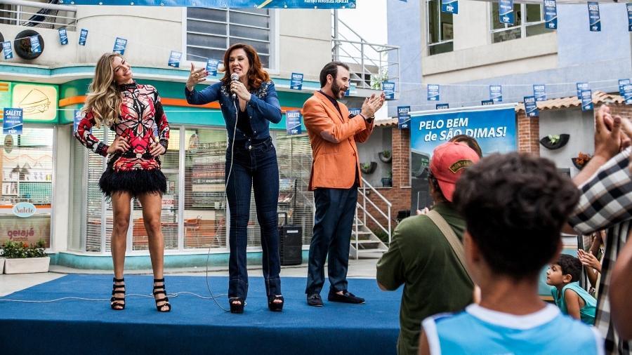 """Salete (Claudia Raia) discursa e Luciane (Grazi Massagera) tenta chamar a atenção ao lado de Hércules (Danilo Grangheia) em cena desta sexta de """"A Lei do Amor"""" - Raquel Cunha/Divulgação/TV Globo"""
