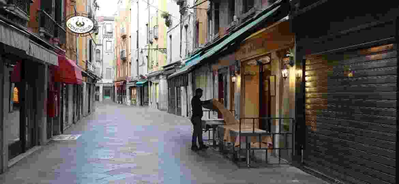 Garçom arruma a mesa de restaurante em rua vazia em meio ao surto do coronavírus em Veneza, na Itália - Marco Di Lauro/Getty Images