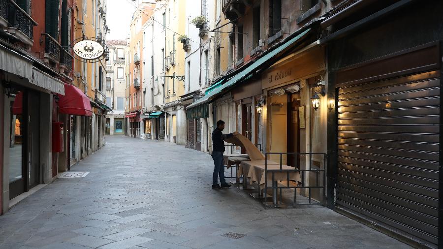 Garçom arruma mesa de restaurante em rua vazia em meio ao surto do coronavírus em Veneza, na Itália - Marco Di Lauro/Getty Images
