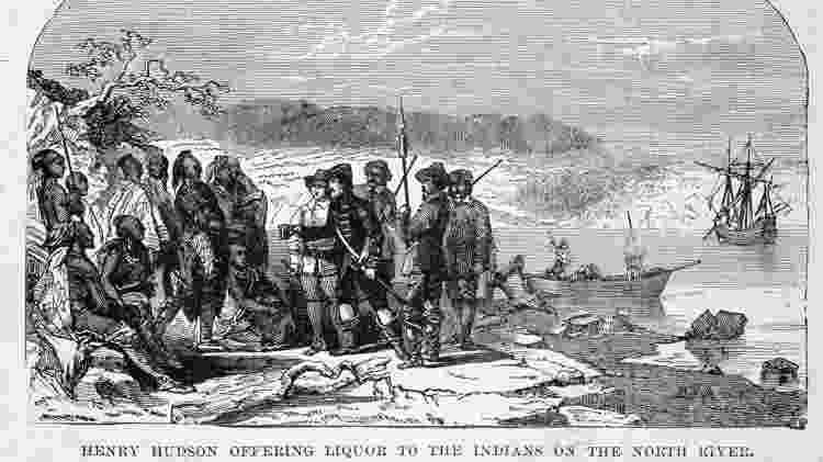 Gravura de 1609: o explorador britânico Henry Hudson (1565 - 1611) oferece álcool a nativos americanos durante expedição no North River (hoje Hudson River)  - Getty Images - Getty Images
