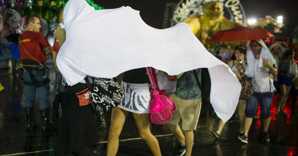 5.jan.2015 - Foliões se escondem da chuva no Sambódromo do Anhembi na primeira noite de desfiles