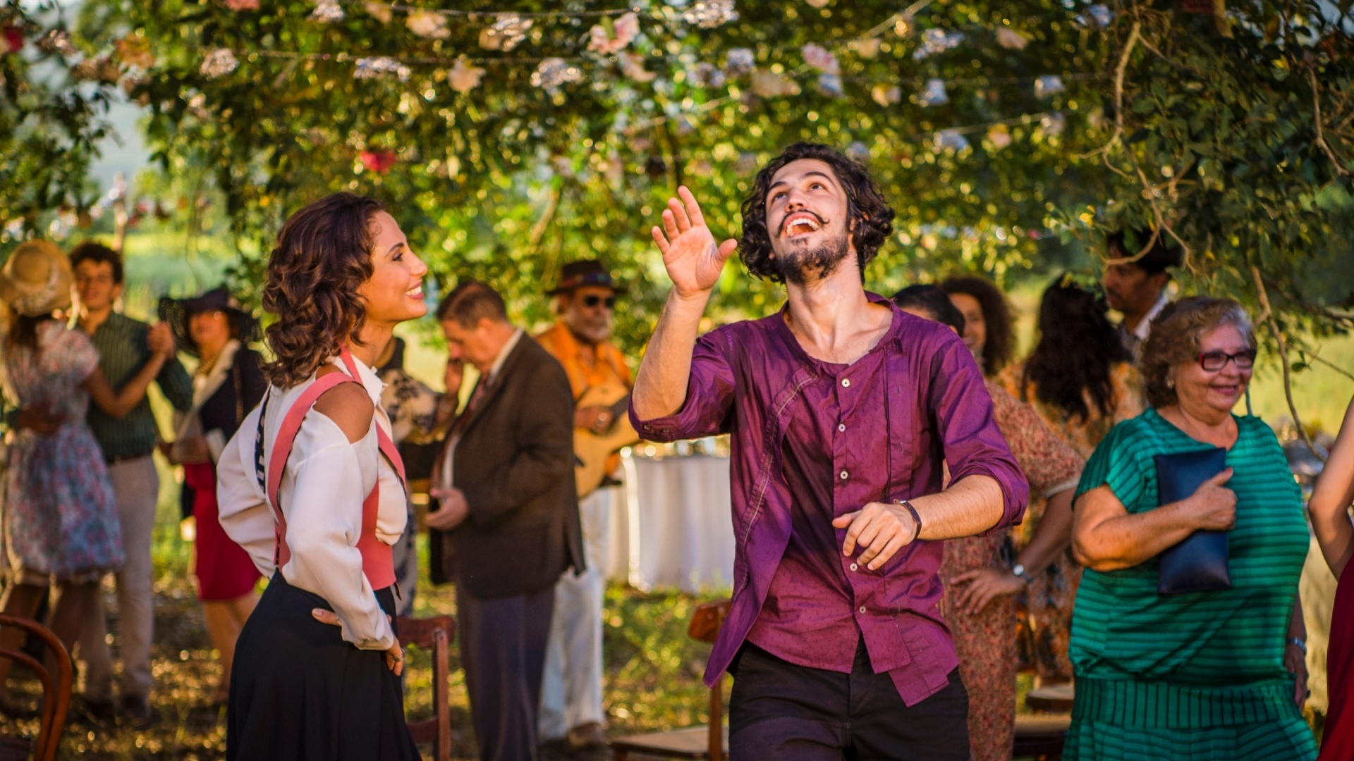 29.abr.2016 - Miguel (Gabriel Leone) brinca com chapéu enquanto dança com a mãe, Tereza (Camila Pitanga), na festa em homenagem ao rapaz, em Grotas do São Francisco