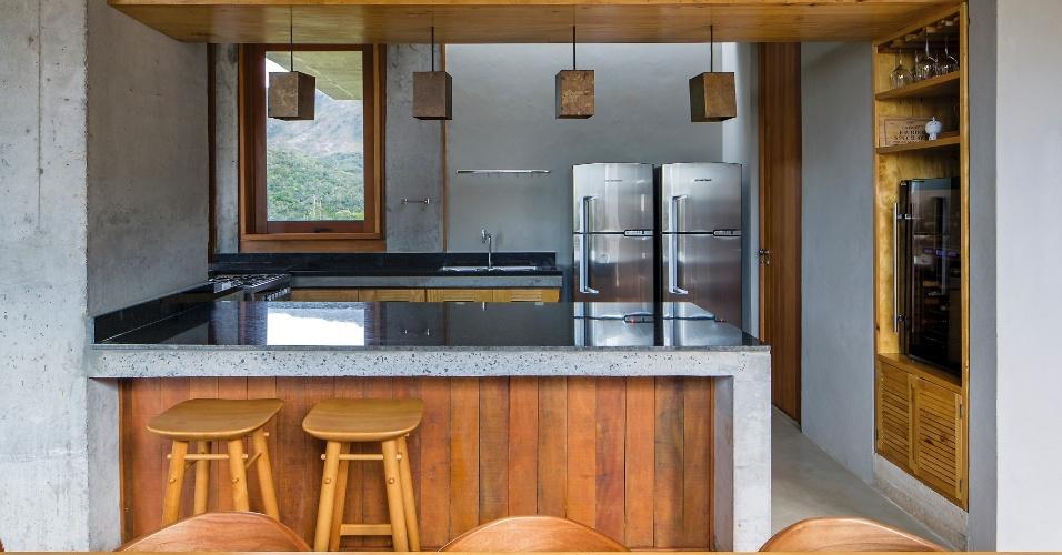 A cozinha da Casa do Bomba é totalmente integrada à sala de jantar e possui balcão que funciona como bar, ao lado da adega. O projeto leva a assinatura do escritório Sotero Arquitetos