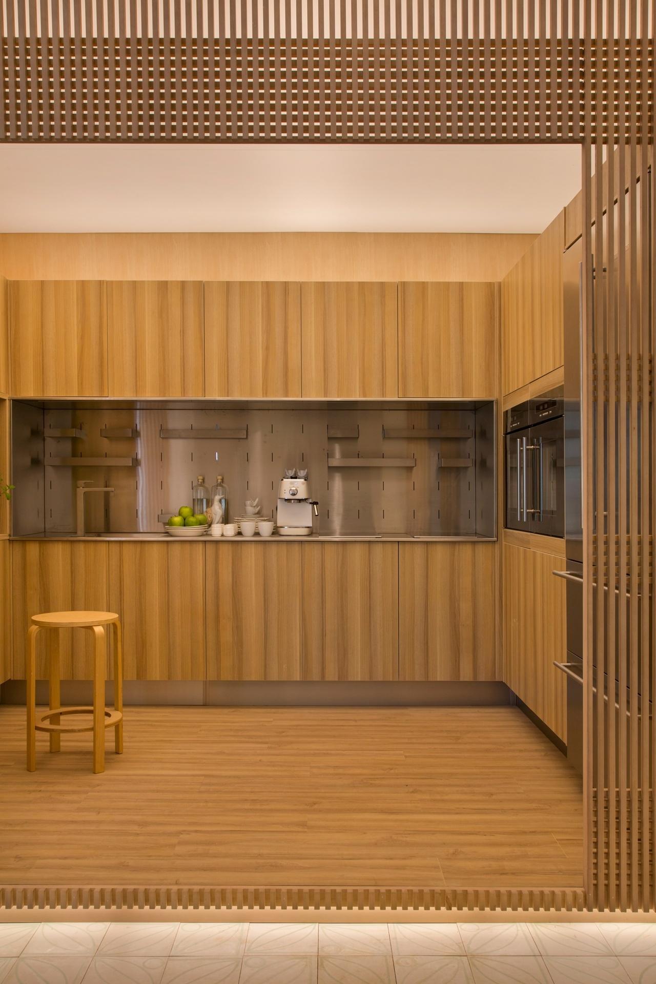 Casa Cor SP 2016 - ambiente Shoji 04: A cozinha fica encaixotada no projeto do escritório Yamagata Arquitetura. No ambiente, a madeira clara predomina e, para dar um aspecto leve à estrutura, a iluminação foi parcialmente instalada atrás dos painéis e logo abaixo do degrau