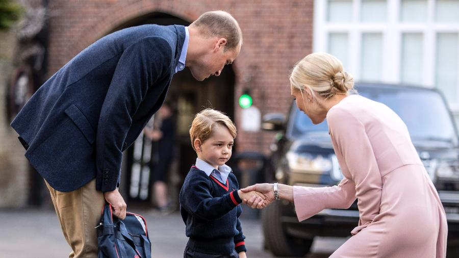 Príncipe George e o o pai, William, cumprimentam a diretora da escola  - AFP
