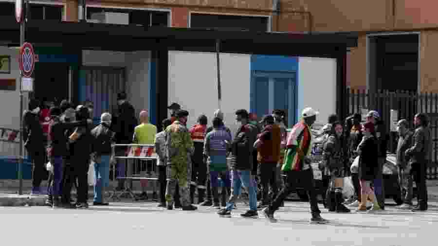 Pessoas na fila para receber a refeição de voluntários em Bari, na Itália - Donato Fasano/Getty Images